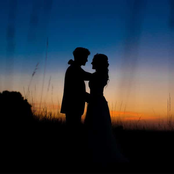 Bride and groom silhouette in a field