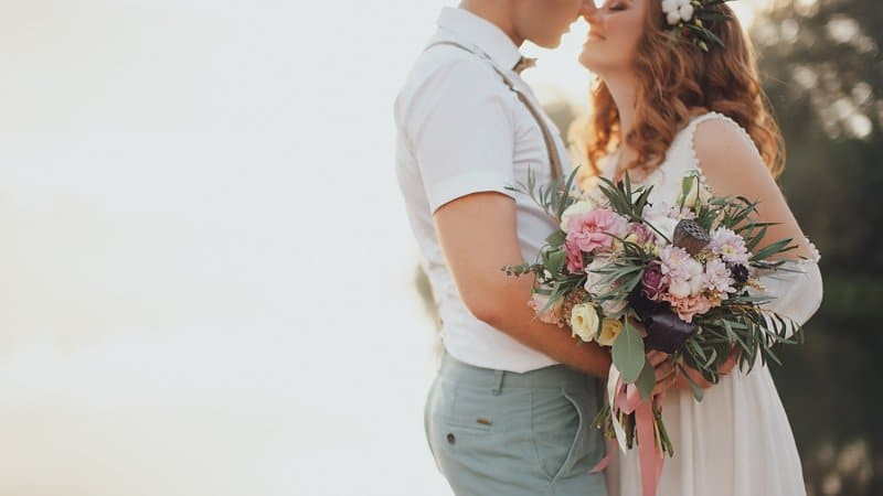 Bride and groom wedding photography with bouquet of flowers