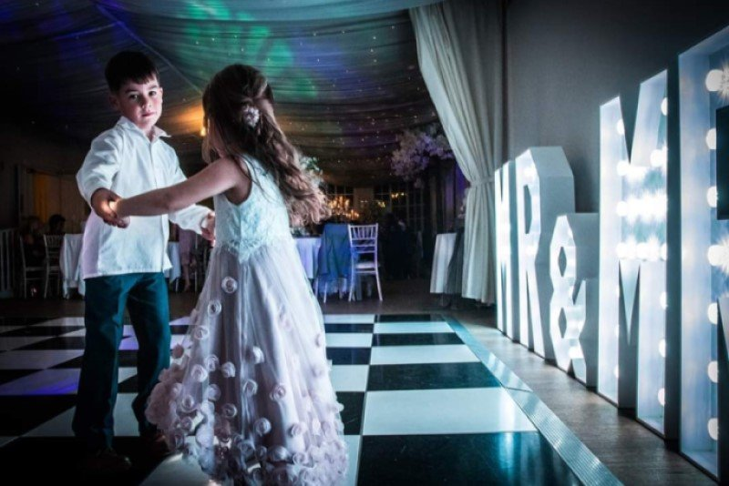 two children dancing with light up letters