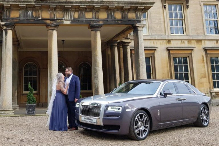 Luxury wedding car outside venue with couple